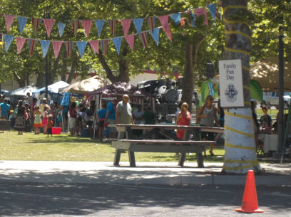 picture of the entrance to fun day with flags and row of game booths